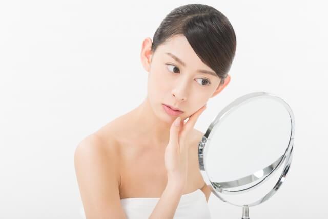 鏡で肌をチェックする女性の画像